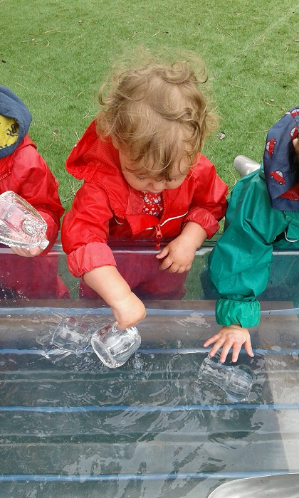 Today, pre-toddlers explored in the water tray in the garden. The children have recently shown a real interest in water play and love to splash in the water and use resources to fill and empty containers.