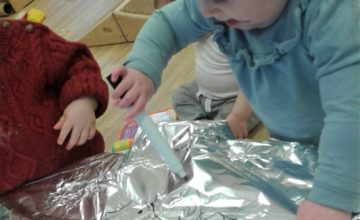 In the Baby room we have been using our white board pens to make marks on the shiny foil.