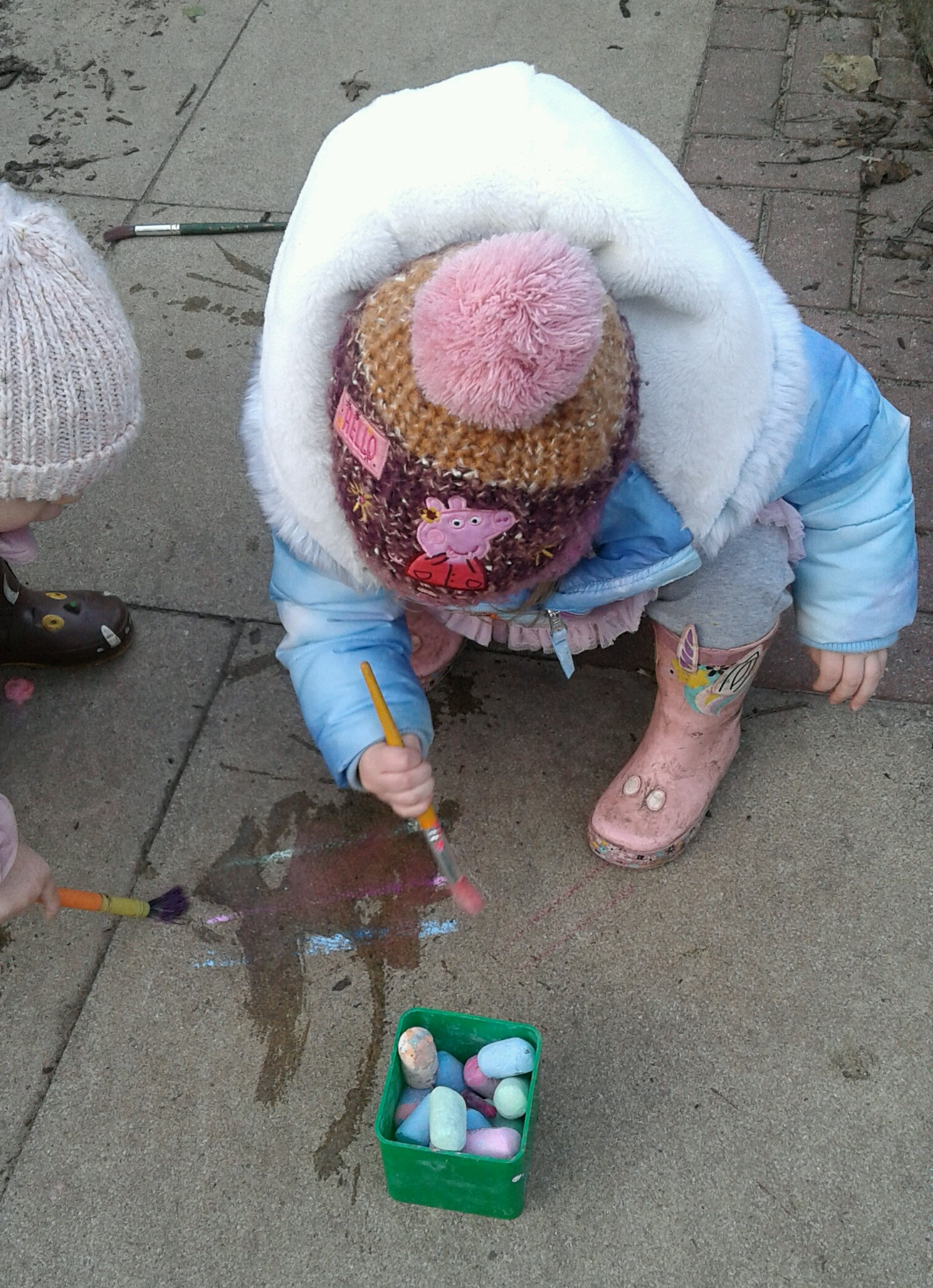 Outside in the garden the Toddlers have been exploring mark making and colour mixing using paint brushes, water and chalks.