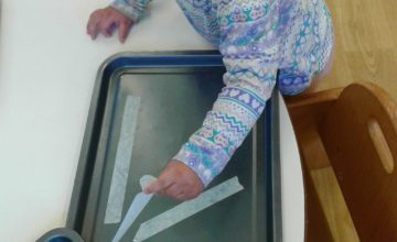 The Babies have been having a great time developing their fine motor skills and concentration by peeling masking tape off of baking trays.