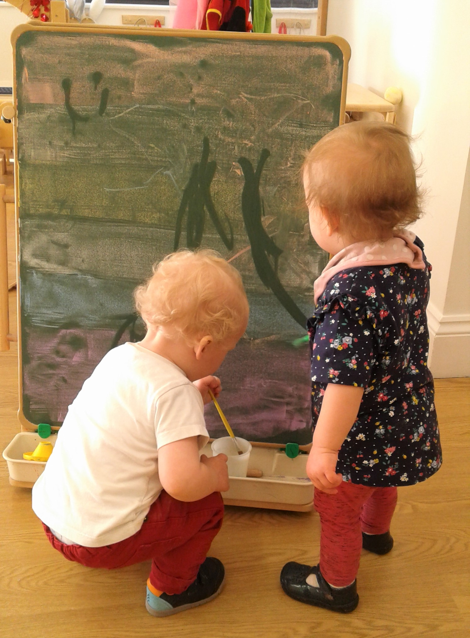 Today we made a rainbow on our chalk board, we then used paintbrushes dipped in water to make marks over the rainbow.